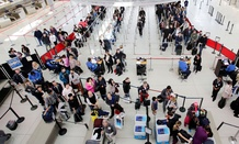 Passengers line up to pass through the TSA security before boarding flights at John F. Kennedy International Airport.