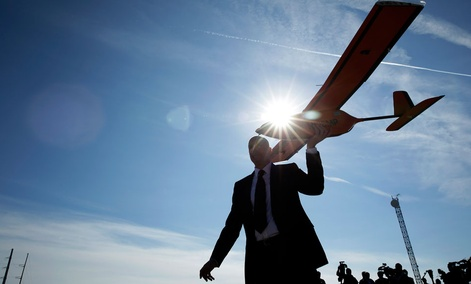 Dan Johnson of Sensurion Aerospace carries the Sensurion Aerospace Magpie commercial drone during an event Friday, Dec. 19, 2014, near Boulder City, Nev.