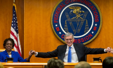 FCC Chairman Tom Wheeler  joins hands with FCC Commissioner Mignon Clyburn before the start of their open hearing and vote on Net Neutrality.