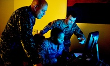 Three military cyber professionals conduct an exercise during Cyber Flag 13-1, Nov. 8, 2012, at Nellis Air Force Base, Nev.