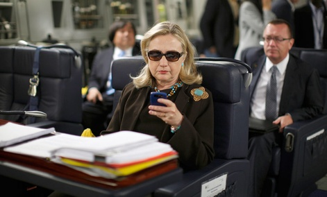 Then-Secretary of State Hillary Rodham Clinton checks her Blackberry from a desk inside a C-17 military plane upon her departure from Malta.