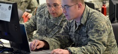 Army Sgt. 1st Class Michael Deblock, Vermont Army National Guard Computer Network Defense Team, left, discusses new ways to make the exercise more challenging for cyber defenders with a fellow Red Cell team member during a 2014 Cyber Shield exercise.
