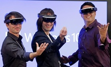 "Microsoft's Joe Belfiore, from left, Alex Kipman, and Terry Myerson playfully pose for a photo while wearing ""Hololens"" devices."