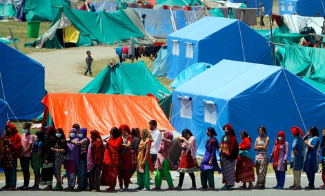 People who have had their homes damaged and are living in tents during the April 25 earthquake line up for drinking water and packed noodles in Kathmandu, Nepal.