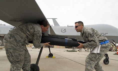 Two Air Force NCOs load munitions on an MQ-9 Predator.
