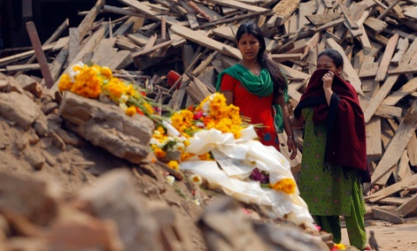 Nepalese women look at floral tributes placed in memory of victims killed in the earthquake, at Basantapur Durbar Square in Kathmandu, Nepal, Thursday, May 7, 2015.