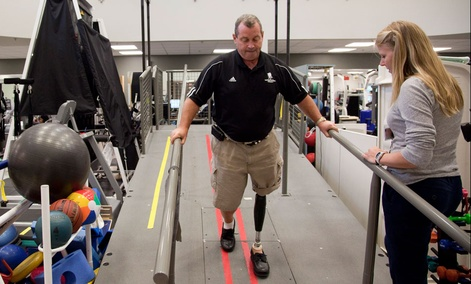 Vietnam veteran John Loosen, who lost a leg in Vietnam, shows off a new microprocessor-controlled prosthetic knee during a photo opportunity with his physical therapist Lindsay Martin, right, Wednesday, Aug. 18, 2010, at Walter Reed Army Medical Center.
