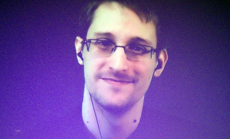 Former U.S. National Security Agency contractor Edward Snowden, who is in Moscow, is seen on a giant screen during a live video conference for an interview with Amnesty International.