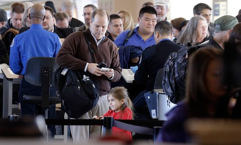Travelers wait in line to check in at a security checkpoint area at Midway International Airport.