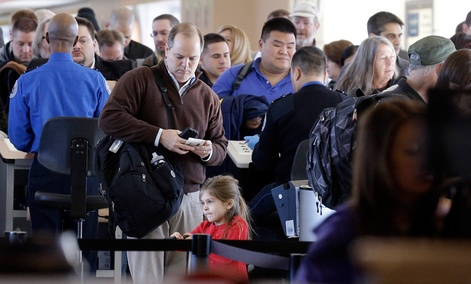 Travelers wait in line to check in at a security checkpoint area at Midway International Airport, Friday, Nov. 21, 2014, in Chicago.