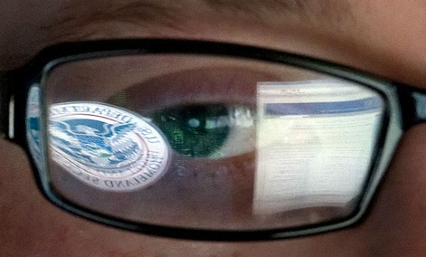 A reflection of the DHS logo is seen reflected in the glasses of a cybersecurity analyst in the watch and warning center at DHS' secretive cyber defense facility in Idaho.