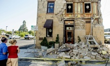 Pedestrians examine a crumbling facade following an earthquake in Napa, California.