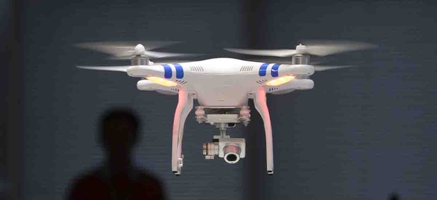 A staff member from DJI Technology Co. demonstrates the remote flying with his Phantom 2 Vision+ drone.