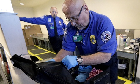 A TSA agent checks a bag at a security checkpoint area at Midway International Airport.