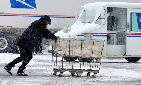 USPS carrier Stephanie Starr, of Seymour, pushes a mail cart from her carrier vehicle to the loading dock area of the Columbus, Ind. Post Office.