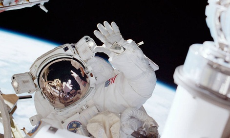 Astronaut Carlos I. Noriega, mission specialist, waves toward his partner, astronaut Joseph R. Tanner during a space walk.