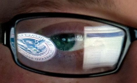 A reflection of the Department of Homeland Security logo in the eyeglasses of a cybersecurity analyst.