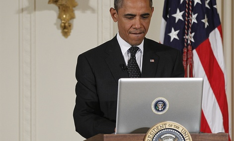 """President Barack Obama uses a laptop computer to send a tweet during a """"Twitter Town Hall"""" in the East Room of the White House."""