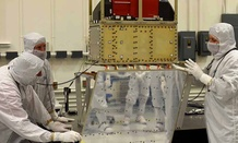 Ball Aerospace technicians lower the ATMS instrument onto the JPSS-1 spacecraft.