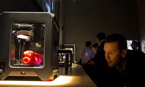 Trade show attendees examine the MakerBot Replicator Mini 3D printer at the International Consumer Electronics Show, Wednesday, Jan. 8, 2014.