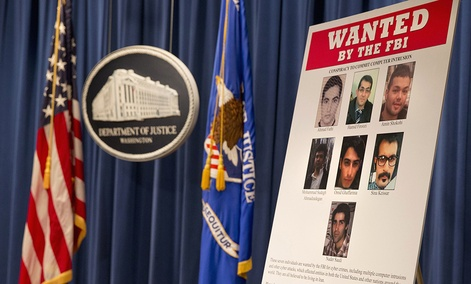 A poster lists Iranians who are wanted by the FBI for computer hacking, during a news conference at the Justice Department in Washington, Thursday, March 24, 2016.