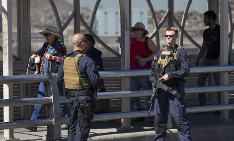 Pedestrians cross into Juarez, Mexico as U.S. Customs and Border Protection officers of the Special Response Team unit, patrol the Paso del Norte Port of Entry in El Paso, TX.