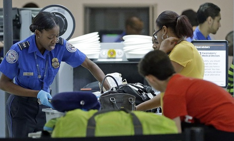 A TSA officer checks travelers luggage to be screened by an x-ray machine at a checkpoint at Fort Lauderdale-Hollywood International Airport.