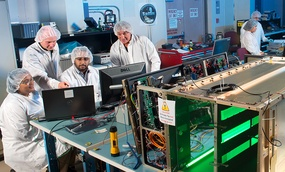 A team of scientists and engineers test the components of Saffire I (background) and Saffire II (foreground)