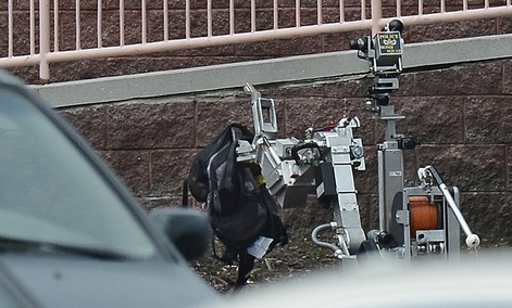 Nashville Metro Police Bomb Squad robot picks up a backpack on the side of a movie theater following a shooting, Wednesday, Aug. 5, 2015, in Antioch, Tenn.