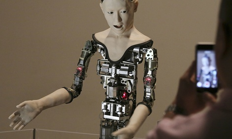 """A visitor takes photos of the humanoid robot """"Alter"""" displayed at the National Museum of Emerging Science and Innovation in Tokyo, Monday, Aug. 1, 2016."""