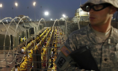 A U.S. soldier stands guard as detainees pray at U.S. military detention facility Camp Bucca, Iraq.