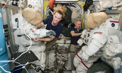 Expedition 48 crew members Kate Rubins (left) and Jeff Williams (right) of NASA outfit spacesuits inside of the Quest airlock aboard the International Space Station.