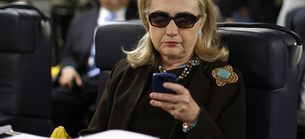 Then-Secretary of State Hillary Rodham Clinton checks her Blackberry from a desk inside a C-17 military plane.