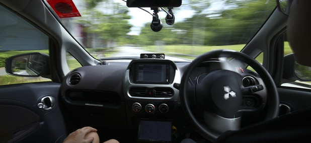 A driver, right, gets his hands off of the steering wheel of an autonomous vehicle during its test drive in Singapore.