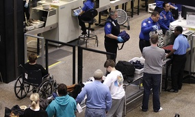 Travelers at Seattle-Tacoma International Airport undergo luggage security screening at a TSA checkpoint.