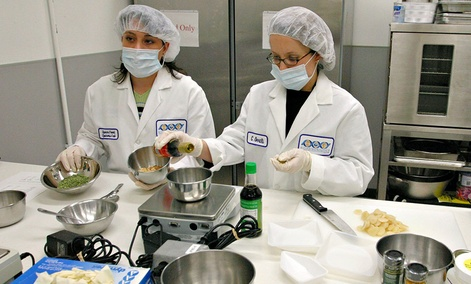 NASA Food Scientists Donna Nabors, left, and Connie Oertli, right, demonstrate how they prepare freeze dried fried rice in the Space Food Systems Laboratory at Johnson Space Center in Texas.