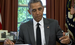 President Barack Obama signs the three-month highway funding bill, Friday, July 31, 2015, in the Oval Office of the White House in Washington.