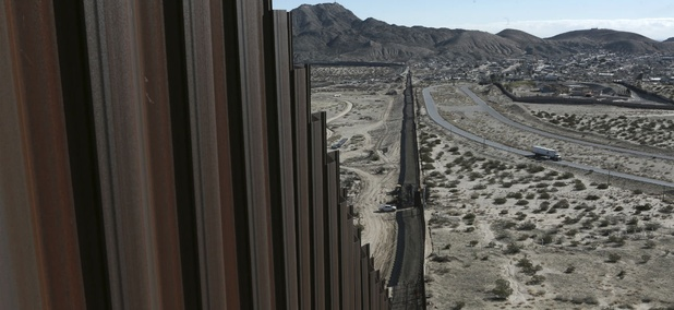A truck drives near the Mexico-US border fence.
