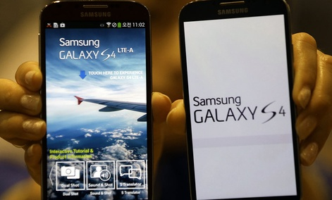 An employee of Samsung Electronics holds the Galaxy S4 LTE-A smartphones at a showroom of its headquarters in Seoul, South Korea, Friday, July 5, 2013.