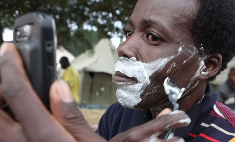 A man shaves himself, using his mobile phone as a mirror at a temporary shelter set up for foreign nationals fleeing attacks from South Africans in and around Johannesburg Sunday, April 19, 2015.