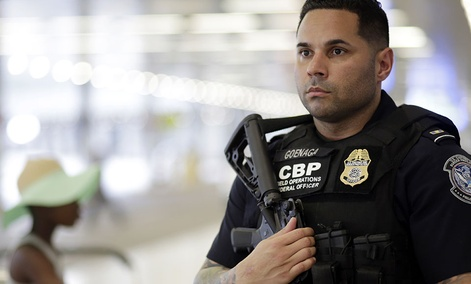 A U.S. Customs and Border Protection officer patrols outside of the departures area at Miami International Airport, Friday, July 1, 2016.