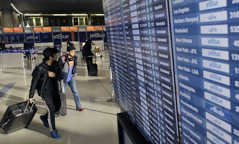 Travelers walk past an airline reader board Tuesday, Nov. 22, 2016, at Logan International Airport, in Boston.