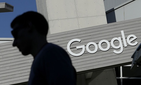 A man walks past a building on the Google campus in Mountain View, Calif. Google said Wednesday, May 11, 2016