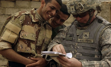 Iraqi Army soldiers look at a book of Arabic phrases as U.S. Army Staff Sgt. Robert Williams, 37, assigned to Delta Co., 1st Combined Arms Battalion, 67th Armor Regiment, looks for help in communicating in Mosul.