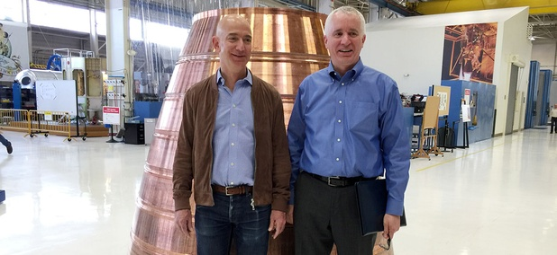 Blue Origin founder Jeff Bezos, left, stands with president Rob Meyerson in front of a copper exhaust nozzle to be used on a space ship engine on the company's research and production floor.