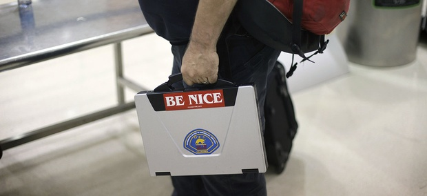 A passenger takes out a laptop with a sticker on it while entering a security checkpoint at Hartsfield-Jackson Atlanta International Airport Thursday, Nov. 18, 2010 in Atlanta.