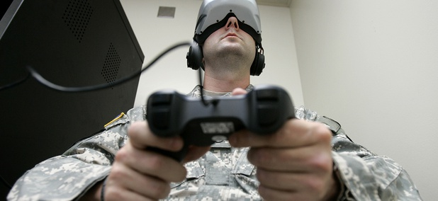 U.S. Army Staff Sgt. Jeff Ebert wears a virtual-reality headset and holds a video-game controller as he demonstrates an experimental virtual-reality computer simulation.