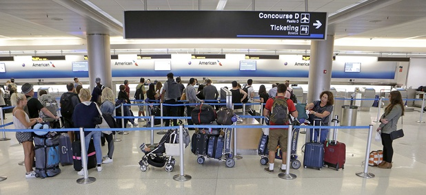 Airline passengers stand in line as they wait to rebook their canceled flight at the American Airlines counter at Miami International Airport, March 13, 2017.