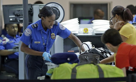A TSA officer checks travelers luggage to be screened by an x-ray machine at a checkpoint at Fort Lauderdale-Hollywood International Airport, May 27, 2016