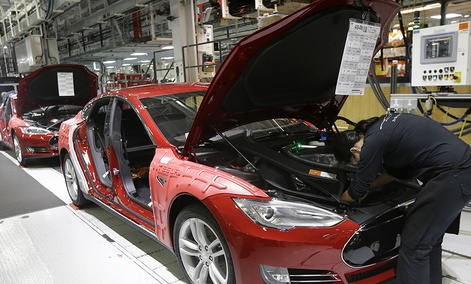 Tesla employees work on a Model S cars in the Tesla factory in Fremont, Calif., Thursday, May 14, 2015.